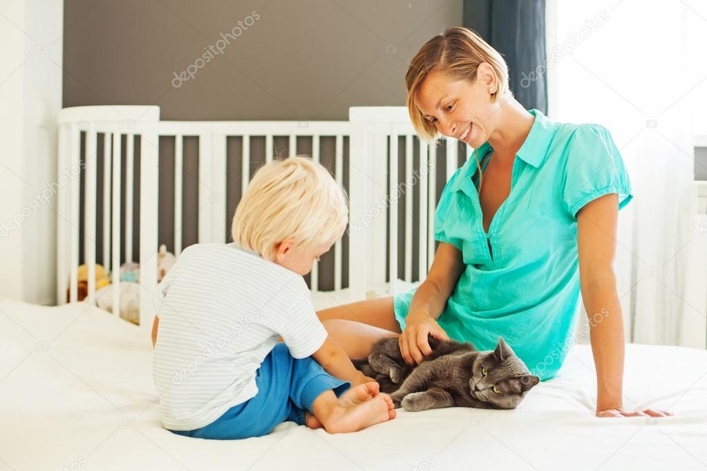 mother and son playing with cat