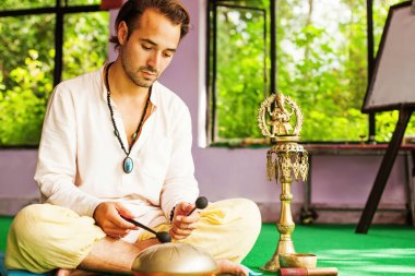 mixed race man playing mantras