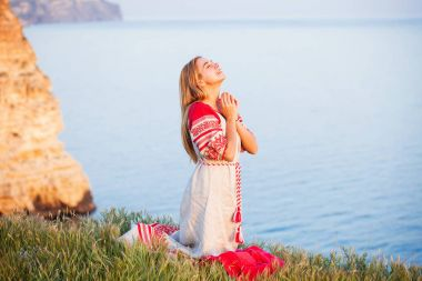 woman wearing traditional russian clothes passionately praying
