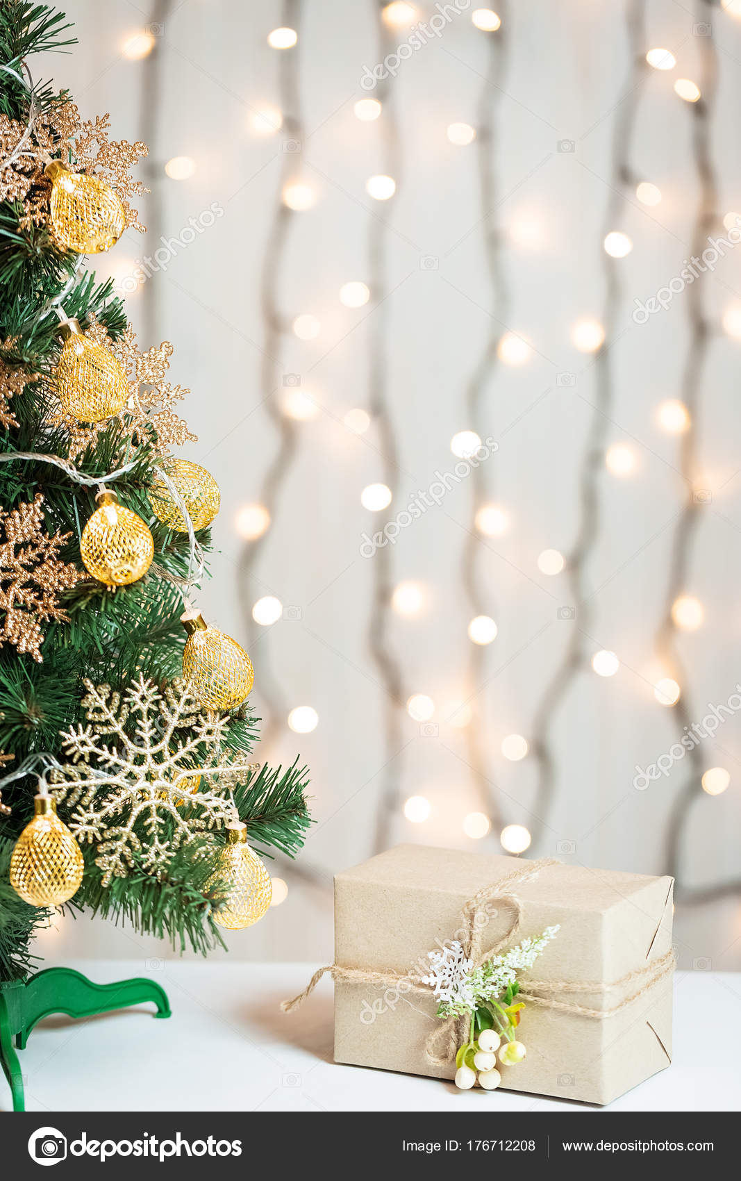 A Christmas tree decorated snowflakes and a garland with gift box on ...