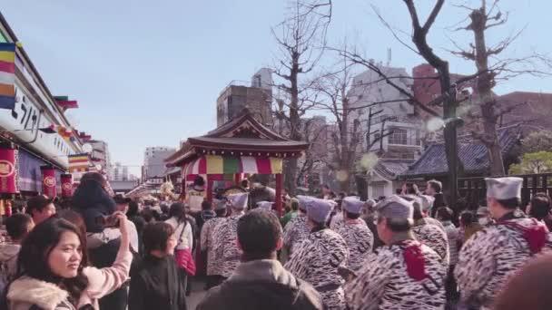 Statické video vozíku, ve kterém sedí hudebníci hrát na bicí, flétnu a šamisen během festivalu Asakusa.