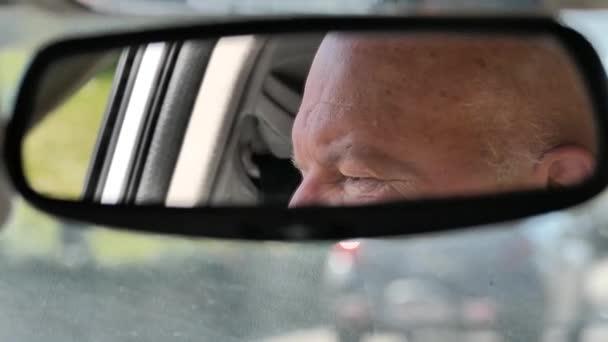 Senior blickt in den Spiegel seines Autos