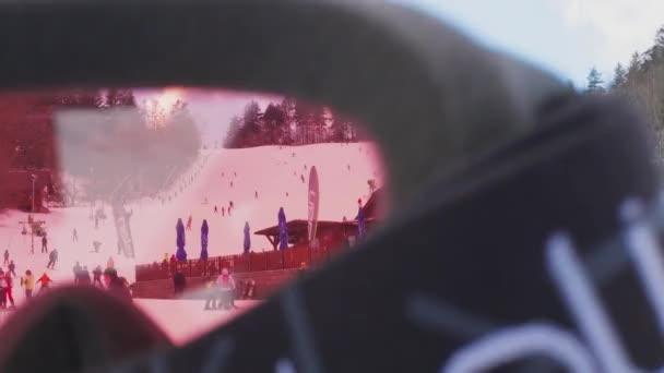 Olešnice, Česká republika - 12 / 13 / 2019: Lyžařské středisko na Moravě přes lyžařské brýle, ruční. Lidé na sjezdovce v lyžařském středisku přes růžové sklo. Lyžaři na horách, děti na sněhu. Horolezecké a lyžařské rodiny. Zimní aktivní sportovní dovolená