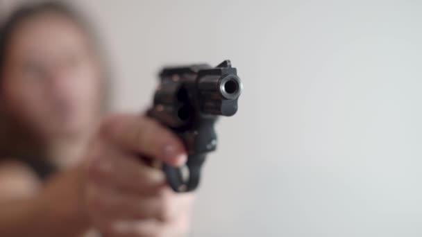 Egy férfi fegyvert fog és lőni készül.