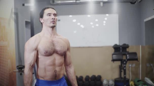 Typ mit schönen Muskeln, Bodybuilder, trainiert Bizeps und Schulter