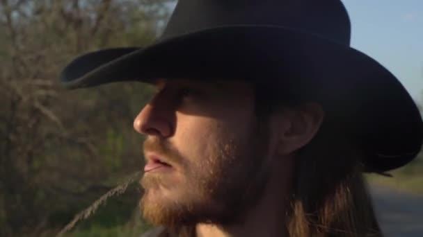 Muž, kovboj, v klobouku s rudým vousem a brčkem v ústech, kráčí po cestě, dívá se na svá pole