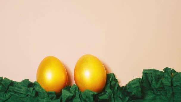 Stop-Motion goldene Eier auf rosa Hintergrund. Osterkonzept. Papierdekoration. Looping-Video. Grüne Wiese 4k