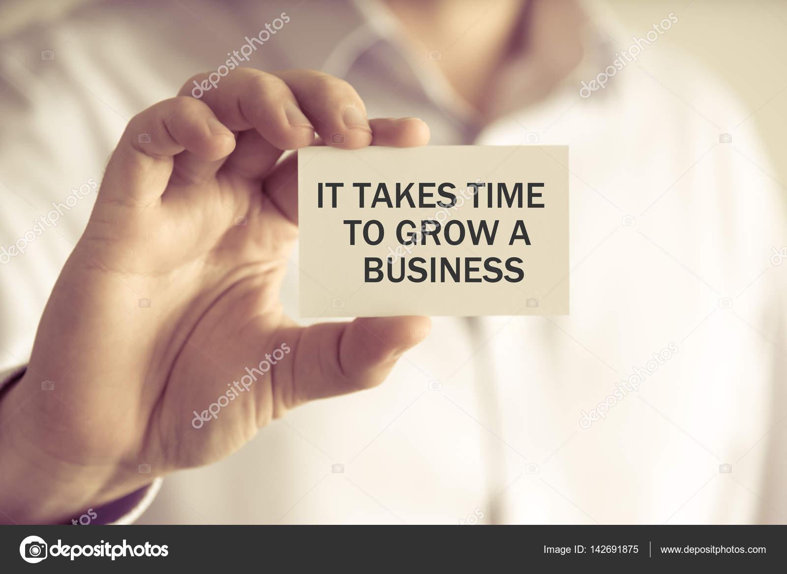 32a63171b4f Closeup no empresário segurando uma placa com o texto que leva tempo para  crescer um negócio
