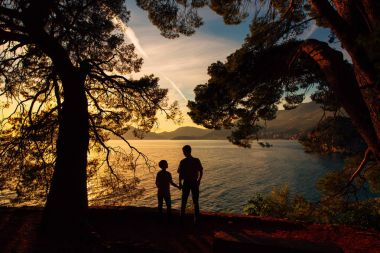 Silhouette of parents and two children at sea at sunset. Montene