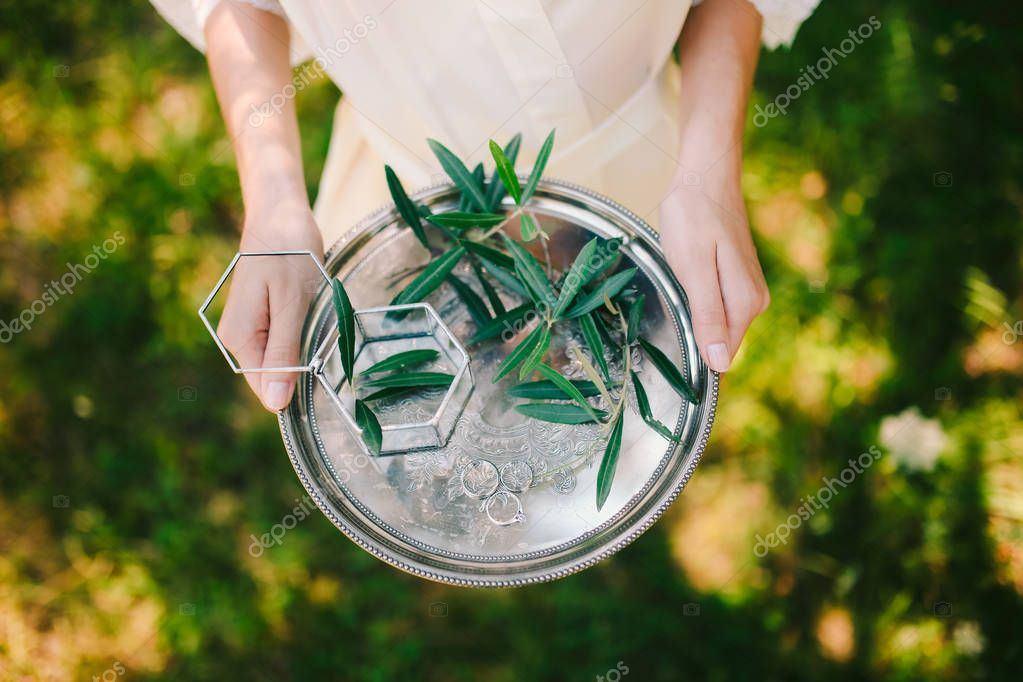 Wedding rings on a silver tray with olive branches in their hand