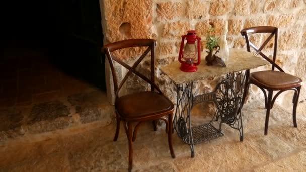 Sedie Depoca : Sedie depoca e un tavolo sullo sfondo di un muro di pietra u2014 video