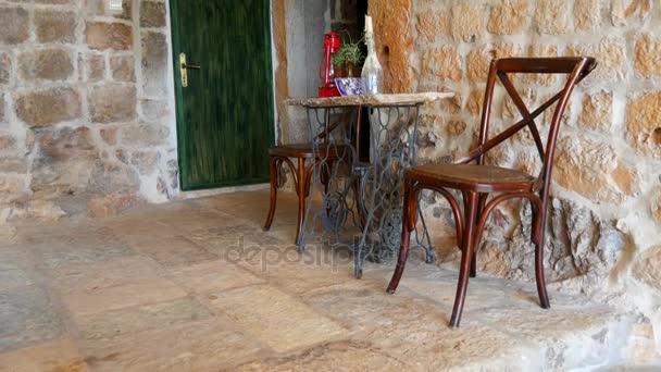 Retro židle a stůl, na pozadí kamenné zdi