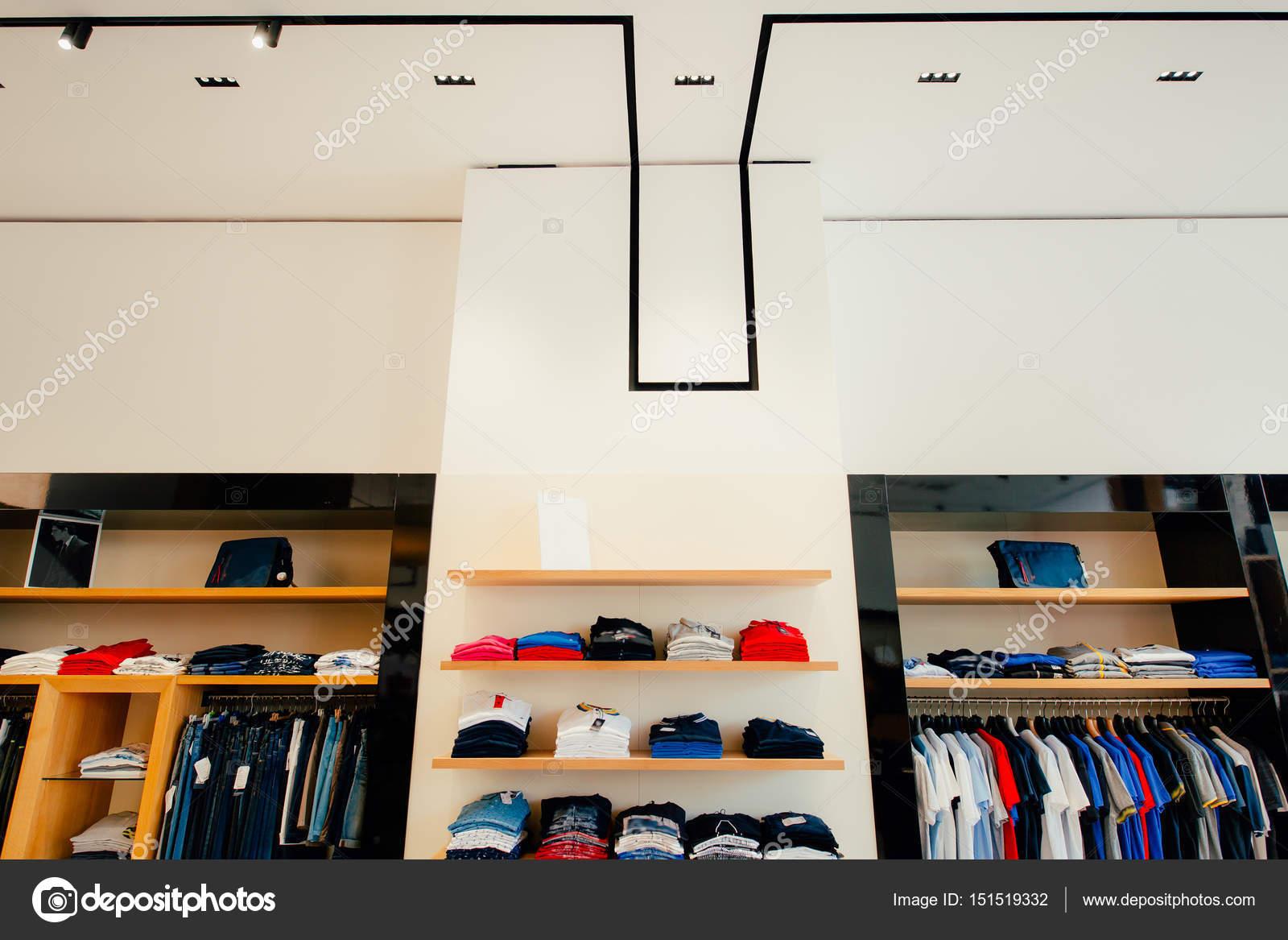 13702034cfe3 Interno di un negozio di abbigliamento. Abbigliamento per uomini e donne  sugli scaffali del negozio. Negozio di abbigliamento di fine hall shopping  — Foto ...