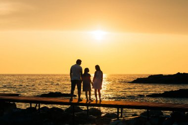 Silhouette of parents with a child at sea. Family on the beach i