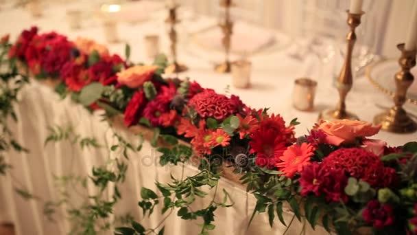 Červené květy na stole novomanžele na svatební hostině