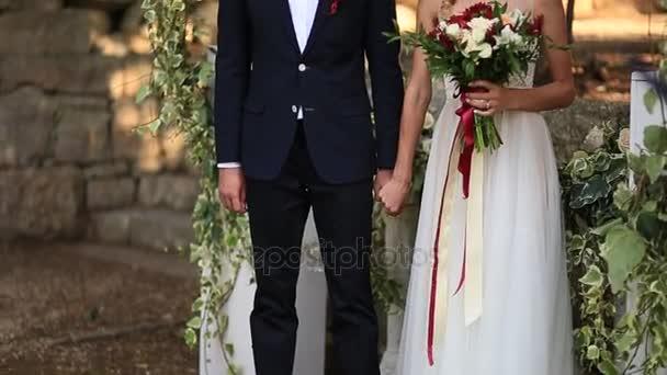 Gli sposi tengono le mani durante la cerimonia di nozze. Della holding delle coppie