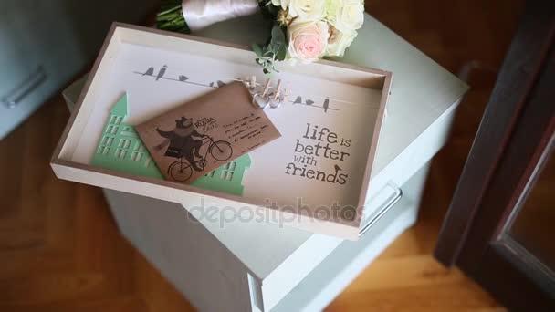 Fedi nuziali su una busta con una lettera con un bouque di nozze