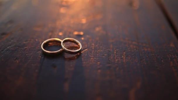 Snubní prsteny na tmavé dřevěné textury při západu slunce