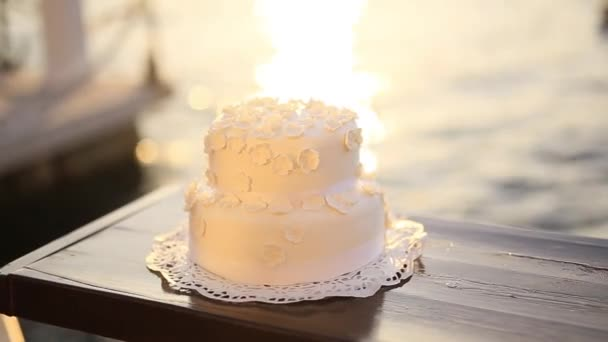Wedding cake on the beach. Glare of the sun on the water. Weddin
