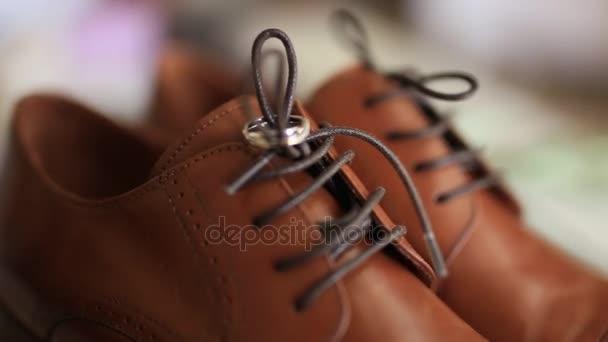 anillos de boda en un zapatos de hombre marrón — vídeos de stock