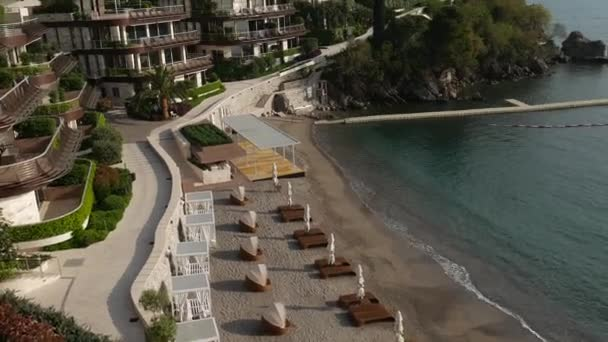 Sun beds and umbrellas on the beach. Montenegrin beaches of the