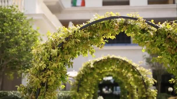 A metal arch overgrown with foliage. The territory of Regent Hot