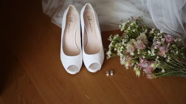 Svatební boty nevěstu na pozadí svatební kytice.