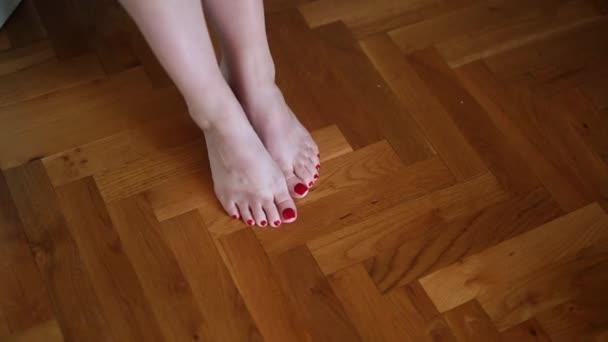 Nahé ženské nohy na podlaze. Malované nehty na nohou červené