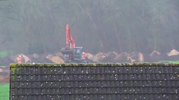 Hitachi bagr pohybující se a kopající společně s pracovníkem, staveniště za deštivého počasí v Rukávu, Nizozemí, 4 stupňů Celsia, 2020