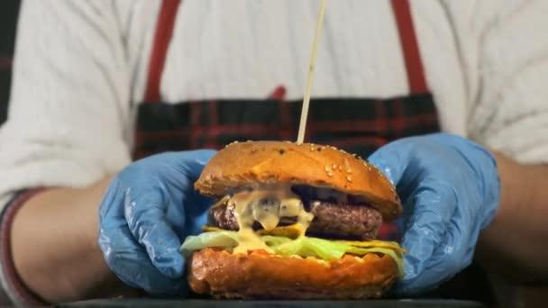 Detail horní pohled na kuchaře ruce vaření hamburger.