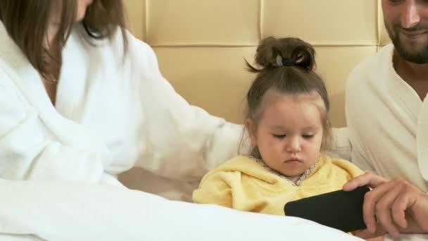 Happy rodina s chytrým telefonem v posteli hotelový pokoj.