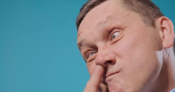 Reifer Schauspieler greift sich Nase mit Finger und zieht lustiges Gesicht zu