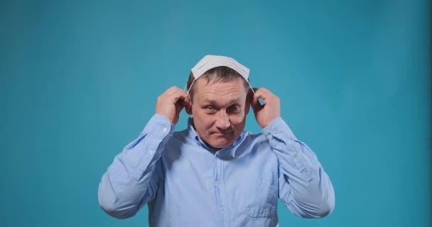 Fremder Mann im blauen Hemd setzt weiße Einwegmaske auf