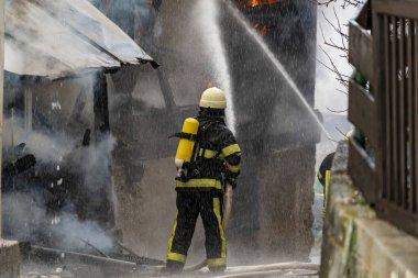 İtfaiyeci evde yangınla mücadele ediyor.
