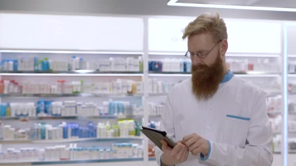 A young pharmacist looks at the tablet and then nods his head approvingly