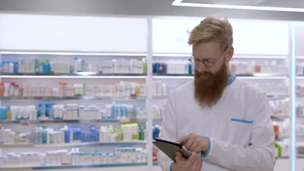 A young doctor or pharmacist uses a tablet and then nods his head approvingly