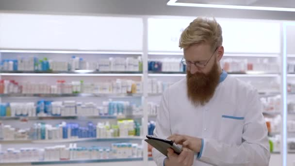 Young pharmacist uses a tablet against the background of medicines