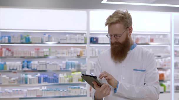 Young handsome doctor or pharmacist uses a tablet against a background of pills