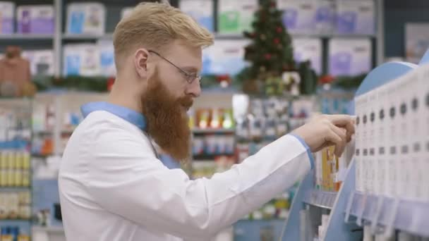 At work. Handsome caucasian or nordic pharmacist standing in semi position near shelves while doing inventory. Slow motion.