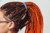 ein Mädchen mit feuerroten Dreadlocks versammelt in einem Pferdeschwanz auf einem weißen Hintergrund Seitenansicht. eine junge Frau mit langen Dreadlocks auf dem Kopf. das Mädchen mit den orangefarbenen Dreadlocks und Piercings