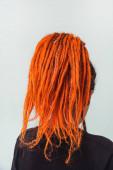 Mädchen mit roten Feuer-Dreadlocks versammelt in einem Schwanz auf weißem Hintergrund Rückansicht. eine junge Frau mit langen Dreadlocks auf dem Kopf. Mädchen ungezwungene Blicke mit orangefarbenen Dreadlocks und Piercings aus nächster Nähe