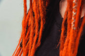 Dreadlocks orange red close-up. Braiding dreadlocks from natural hair. A girl with fiery red dreadlocks back view.