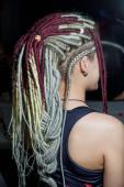 Mädchen mit farbigen künstlichen Dreadlocks und Piercings. Weiße und burgundische Dreadlocks auf dem Kopf einer jungen Frau. Details zum Bild des Mädchens der informellen Kultur