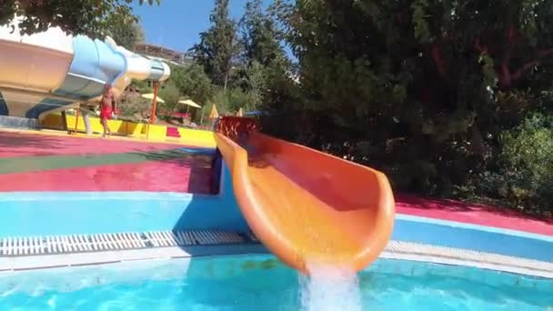 Happy little girl having fun with water slide in a swimming pool enjoying day trip to an aqua amusement park during summer family vacation