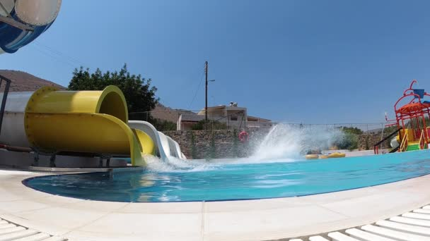 Man having fun in aqua park. He is sliding down from the attraction in slow motion. Thera are a lot of splashes aroun him, Crete, Greece