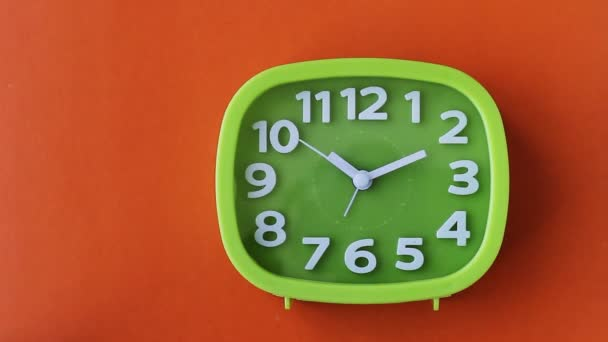 Green clock with white numbers and arrows on orange background, Time Lapse