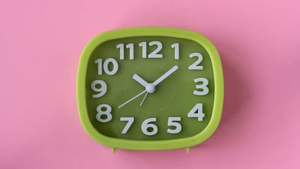 Green clock with white numbers and arrows on pink background, Time Lapse