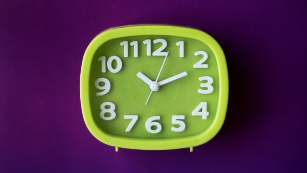 Zelené hodiny s bílými čísly a šipkami izolované na fialovém pozadí, v reálném čase