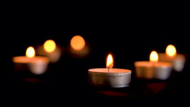 Dekorativní malé svíčky hořet na tmavém pozadí. Malé svíčky. Záběr zblízka. Spousta svíček s mělkou hloubkou. Odpočinek a mír