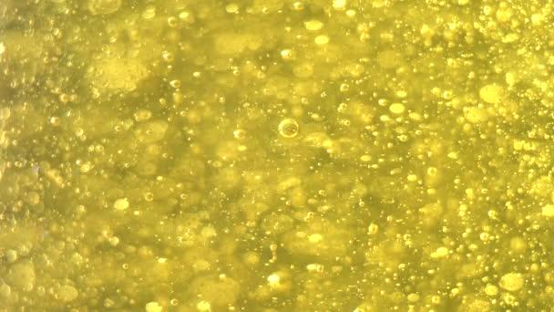 Arany buborékok Lassan kelj fel. Arany háttér. Nagy és kis arany buborékok olaj belül arany folyadék.